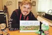 Tomáš Koňařík ukazuje nový kalendář s výběrem komiksů se zubatou žábou.