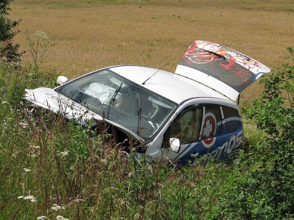 Místo nehody. Dvě osobní vozidla se čelně srazila v linhartovských zatáčkách. Jeden z automobilů skončil v příkopě. Na místě zasahovala policie, hasiči i záchranáři.