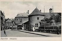 Zámecké náměstí v Krnově. Pamětníci vzpomínají, že vpravo před podloubím byl mléčný bar, kam se chodilo na koktejly, vynikající špičky, gumové hady a další dobroty. Naproti bylo železářství.