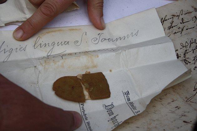 Otevírání schránky zvěže kostela vHolčovicích bylo slavnostní. Mince, noviny a písemné dokumenty bylo možné očekávat, ale jazyk Jana Nepomuckého všechny překvapil.