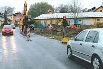 Silnice na Mezinu z Bruntálu. Provoz řídí na třídě Práce semafory, okolo cesty vysekali stromy, silnice je rozřezaná silničářskými stroji.
