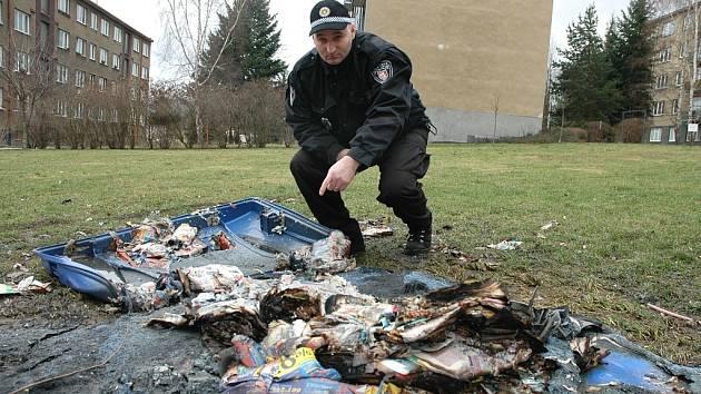 Jeden ze shořelých kontejnerů na boletickém sídlišti. Prohlíží ho strážník Jaroslav Rychnovský.