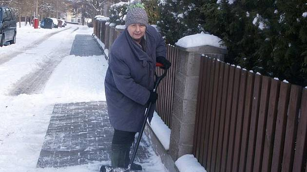 Seniorka Eliška Čalounová zaskakuje za Ústí a odklízí čerstvý sníh před svým rodinným domkem. Úklid by ovšem mělo zajistit dle zákona město.