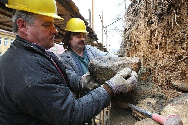 Pracovníci stavební firmy František Hrdlička( vlevo) a Petr Tichý stavějí opěrnou zeď pod skalami v Děčíně.