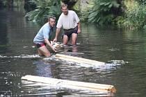 Truhláři Petr Holý a Milan Dont musejí dřevo pro čertovský mlýn splavovat místní říčkou Kamenicí