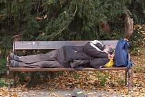 Ve městě na lavičkách spí bezdomovci.