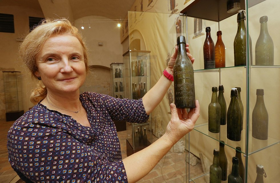 příprava výstavy ředitelka zámku Iveta Krupičková ukazuje pivní láhve uložné ve vitrínách