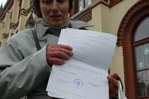 VZALI MI HO!  Nešťastná Eva Bušovská ukazuje před zvláštní školou v Rumburku protokol o předběžném odebrání jejího jedenáctiletého syna. Ten podle svědků dlouhodobě týral svoji babičku.