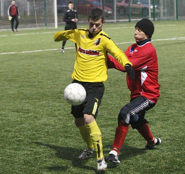 Brankostroj Ústí odstartoval ve druhé půli Martykán (v kulichu), který pak přidal ještě jeden gól. Na snímku bojuje v hustém dešti o míč s děčínským Žáčkem.