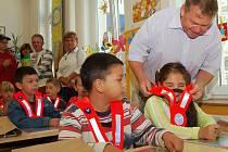 Majitel fotbalového klubu Řezuz Děčín a poslanec parlamentu Vladimír Šoltys rozdával 550 děčínským školákům reflexní kšandičky