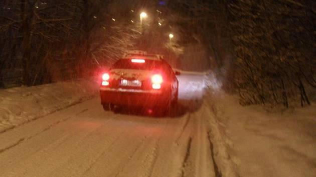 Výjezd ze sídliště Vinařská ulice navečer za sněžení. Foceno dne 28. ledna 2010