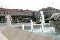 Kráska mezi kašnami stojí před nádražím