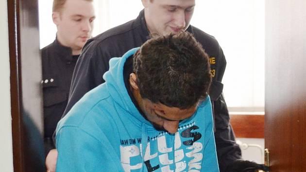 Muž podezřelý z vraždy je odváděn od soudu do vazby.