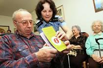 Na snímku vysvětluje policistka z preventivně informační skupiny Oldřichu Mancovi obsah letáku,který policisté rozdávali obyvatelům počovatelského domu pro seniory.