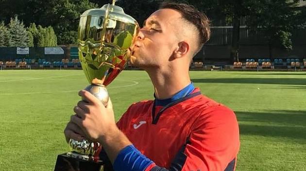 BRANKÁŘ Jiří Vosecký dal v Kadani jeden ze tří gólů Jílové. Na snímku se mazlí s pohárovou trofejí.