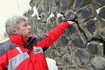 PUKLINY VE ZDI. Majitel jednoho z domů Radek Kotrba ukazuje, jak velké trhliny už jsou v opěrné zdi.