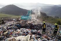 Na místě je rypadlo. Rozhrabává odpad. Hasiči jej prolévají.