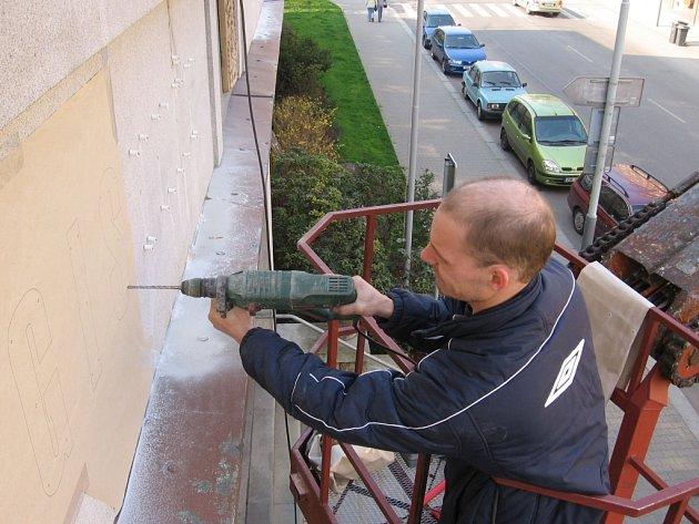 Pracovníci sundavají starý nápis.
