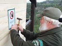 Strážce Jan Lobotka přitlouká varovné cedule na uzavřený altán na Mariině skále.