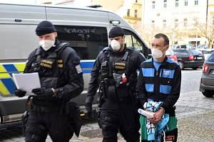 Eskorta přivádí k soudu muže obviněného z pokusu vraždy a přípravy znásilnění matky