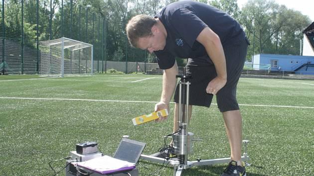 Zástupce z certifikované laboratoře FIFA ve Skotsku právě měří absorpci a deformaci umělého trávníku na Městském stadionu v Děčíně.