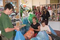 Kluci a děvčata ze separačního kamanda připravují vytříděný odpad k odvozu ze školy.