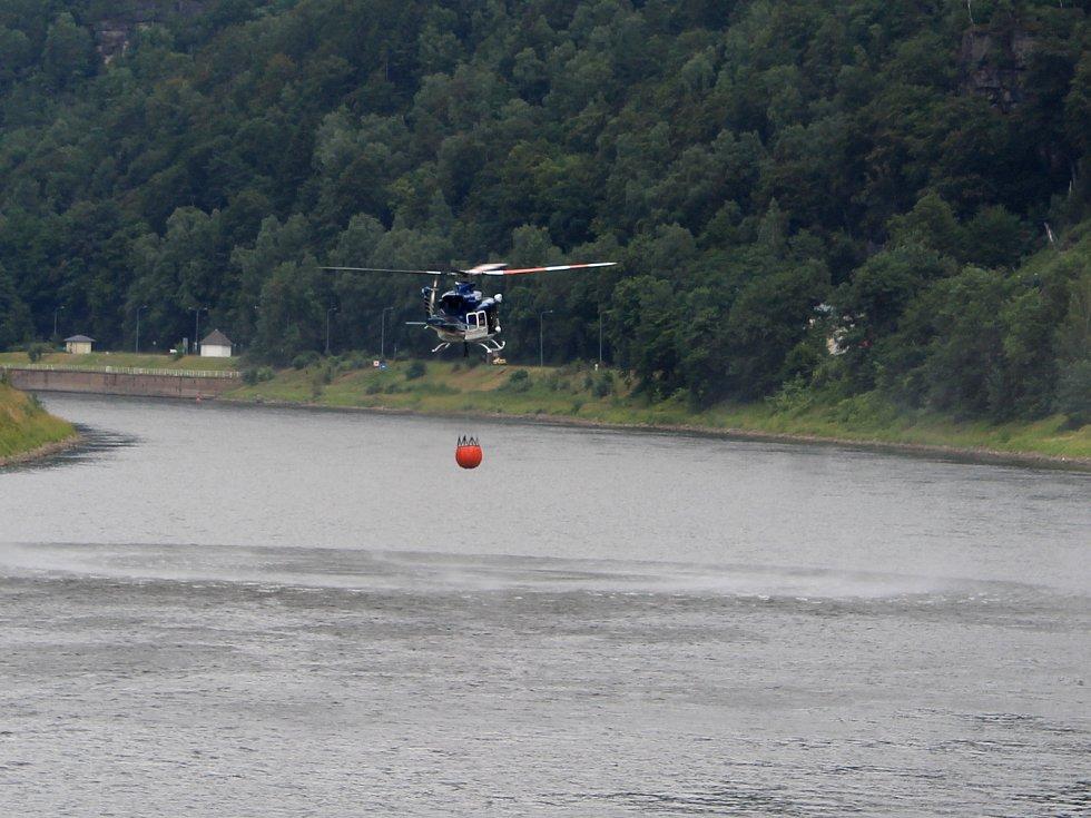 Policejní vrtulník hasí požár u Hřenska