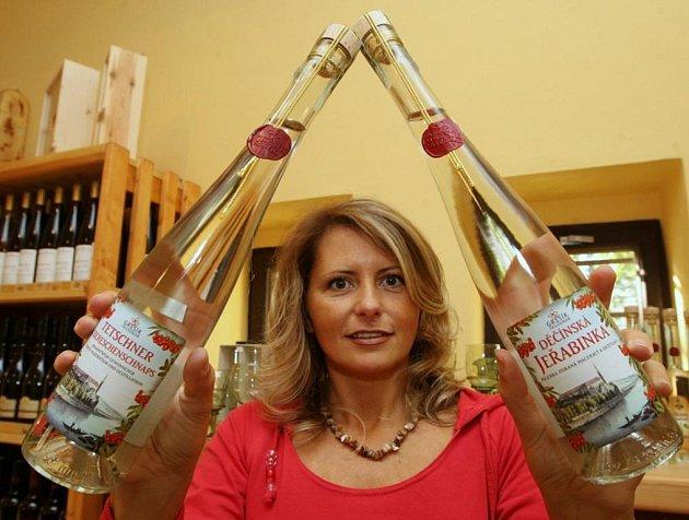 Prodavačka Renata Drasíková ukazuje lahve pálenky s příznačným názvem Děčínská jeřabinka.