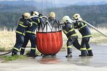 Hasiči cvičí hašení požáru pomocí vodních vaků pod helikoptérou.