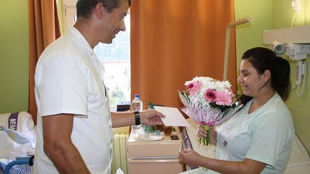 Maminka miminka s číslem 500 si převzala květiny od primáře porodnického oddělení.