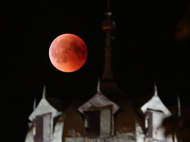 Pohled na úplné zatmění měsíce nad hradem Hazmburk a Litoměřiceme. Letošní oblačnost nepřála obdivovatelům vesmírného divadla a měsíc se objevil na oblože už téměř celý zahalený stínem.