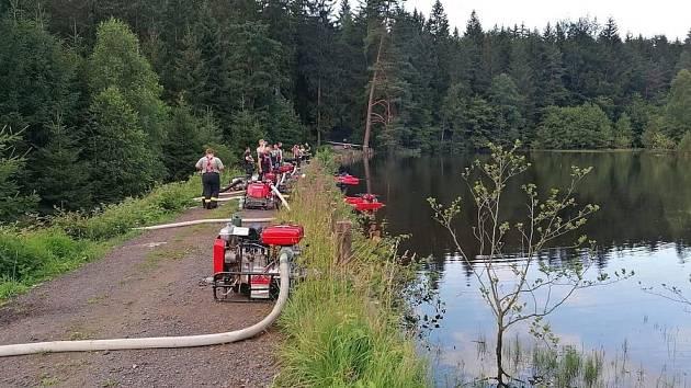 Přetékající Mlýnský rybník u Maxiček. Vodu přečerpávají hasiči