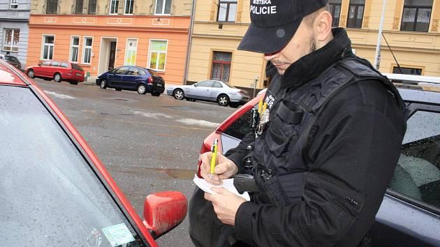 Strážník Městské policie Děčín kontroluje platnost parkovacích karet.