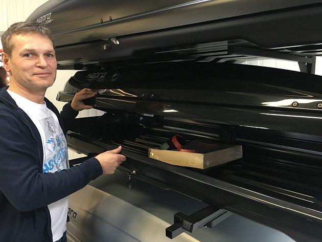 Martin Rigó otevírá střešní box. Lyže a snowboardy se nejlépe přepravují vboxech nebo na nosičích na střeše auta