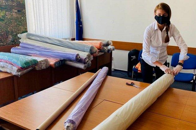 Zasedací místnost radnice se v období koronaviru proměnila ve sklad látky, která je určena pro šití roušek a také v manufakturu, kde dochází k balení balíčků s rouškami.