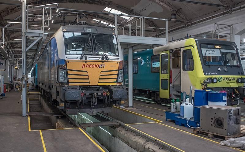 Vozidla zákazníků ELL (lokomotiva Vectron jezdící v nájmu u společnosti RegioJet) a ARRIVA (motorová jednotka 845) během údržby v dílnách Metrans Dyko.