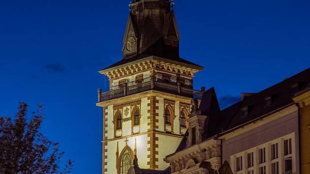 Nasvětlená městská věž, která přímo sousedí s kostelem Nanebevzetí Panny Marie v Chomutvě.