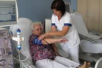 """SESTŘIČKA dialyzačního střediska v Kadani pomáhá pacientce Vlastě Olivové při přípravě na dialýzu. """"Jsem ráda, že už nemusím dojíždět do Chomutova,"""" usmívala se důchodkyně."""