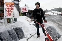 BRIKETY. Mladý vietnamský trhovec nakládá velký pytel s briketami pro německého zakazníka. Na speciální zboží pro Němce lákají i cedule u silnice (malý snímek).
