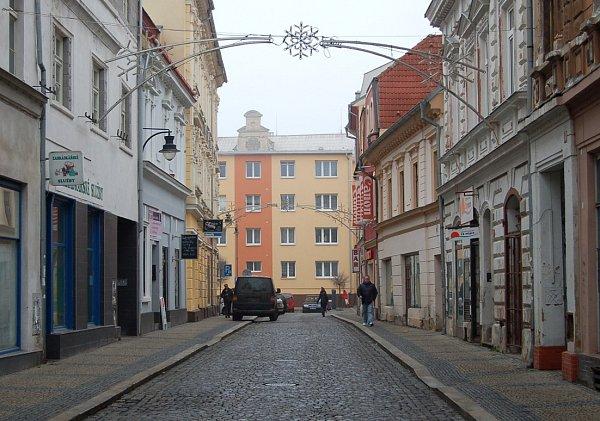 Dnešní pohled. Obytné domy vRevoluční ulici už školu zakrývají skoro celou a místo středověkých prodejen masa je tu třeba kadeřnictví nebo redakce Chomutovského deníku.