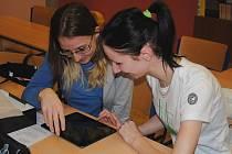 Dvě studentky prvního ročníku jirkovského gymnázia se radují z dárku od města nových tabletů. Používání moderních technologií zatraktivní výuku a umožní rychlé vyhledávání informací.