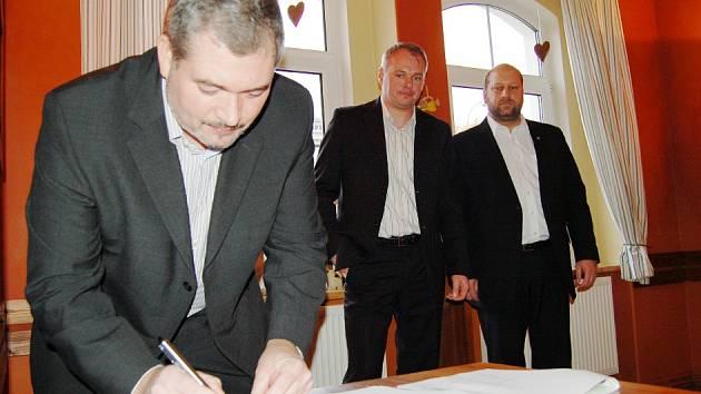 Daniel Černý (PRO Chomutov) podepisuje programové prohlášení tří stran. Za ním Marek Hrabáč (ANO) a Jaroslav Komínek (KSČM).