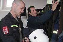 Hasiči Karel Kulhánek (vzadu) a Daniel Pazdera mají stejně jako ostatní na svou výstroj nové skříňky přímo v garáži, aby byla příprava na výjezd co nejrychlejší.