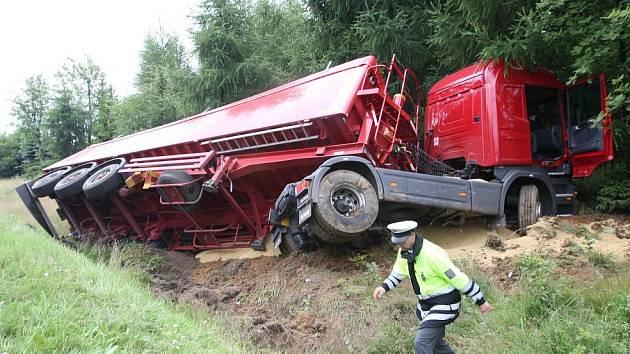 Kamion skončil po srážce s osobním autem zabořený kabinou v lese.