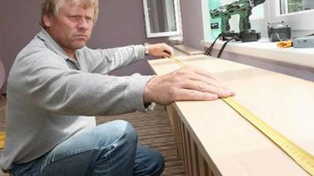 NOVÝ NÁBYTEK. Pracuje je venku i uvnitř. Pracovník právě přeměřuje část dřevěného nábytku. Místnosti získaly i nové koberce.