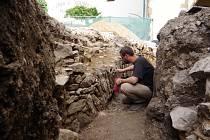 Archeolog Kryštof Derner zkoumá pozůstatky hradeb v místě, kde překonávaly příkop.