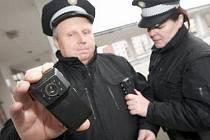 KAMERY. Minikamerky připnuté na hrudi uniformy využívají strážníci v Jirkově na Chomutovsku. Strážnice Jana Zakouřilová pomáhá s připínáním minikamerky svému kolegovi Jaroslavu Zádovi.