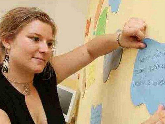 PRAVIDLA. Koordinátorka centra Iva Vondráčková vylepuje na stěnu jedné z místností pravidla, která platí pro využívání centra. Tohle například upozorňuje, že  se nepoužívají vulgární výrazy.