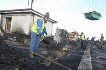 ÚKLID. Zaměstnanci sanační firmy nyní pracují na odklízení následků mohutného požáru střechy panelového domu v Jirkově. Ze střechy musí zmizet zhruba třicet tun odpadu.