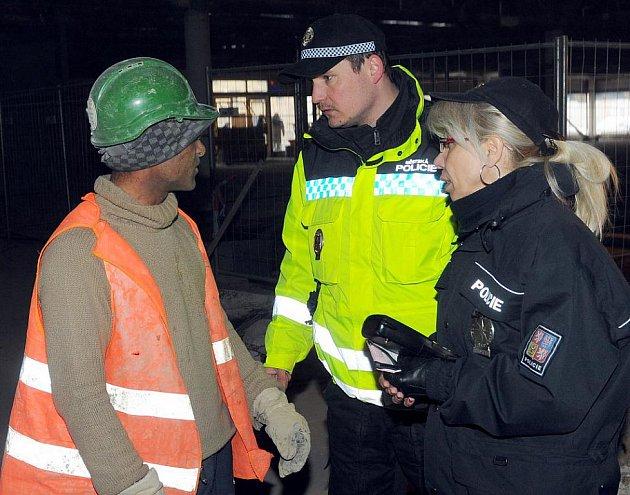 Policistka a strážník lustrují jednoho z dělníků.
